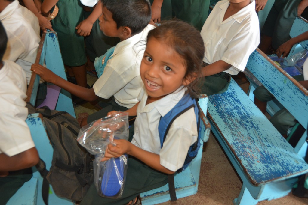 A student of the Barabina Primary School smiles brightly after receiving his new pair of shoes!
